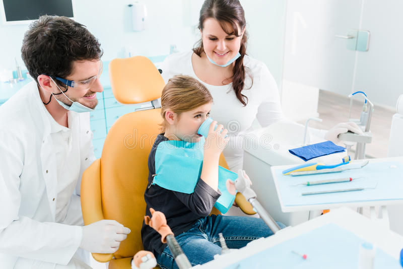 Дантист обрабатывая ребенка в его хирургии стоковые фотографии rf
