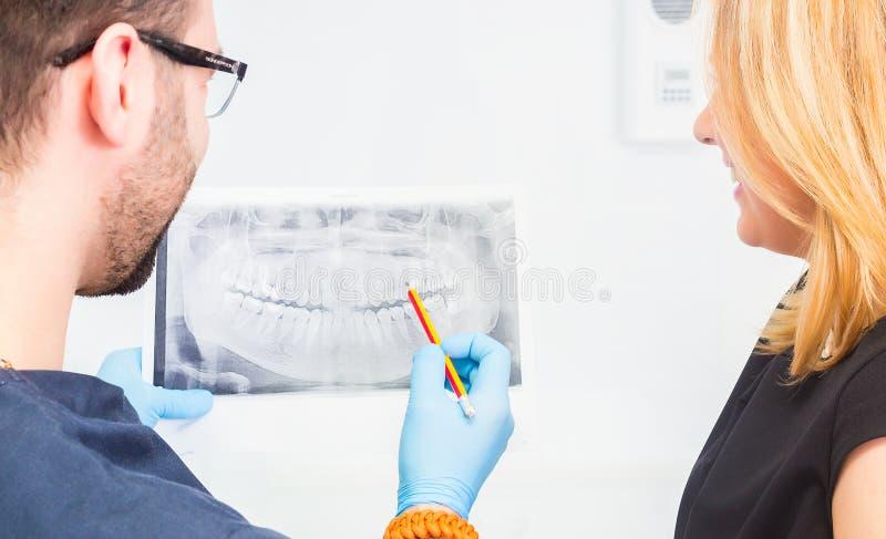Дантист объясняя изображение луча x к пациенту стоковое фото