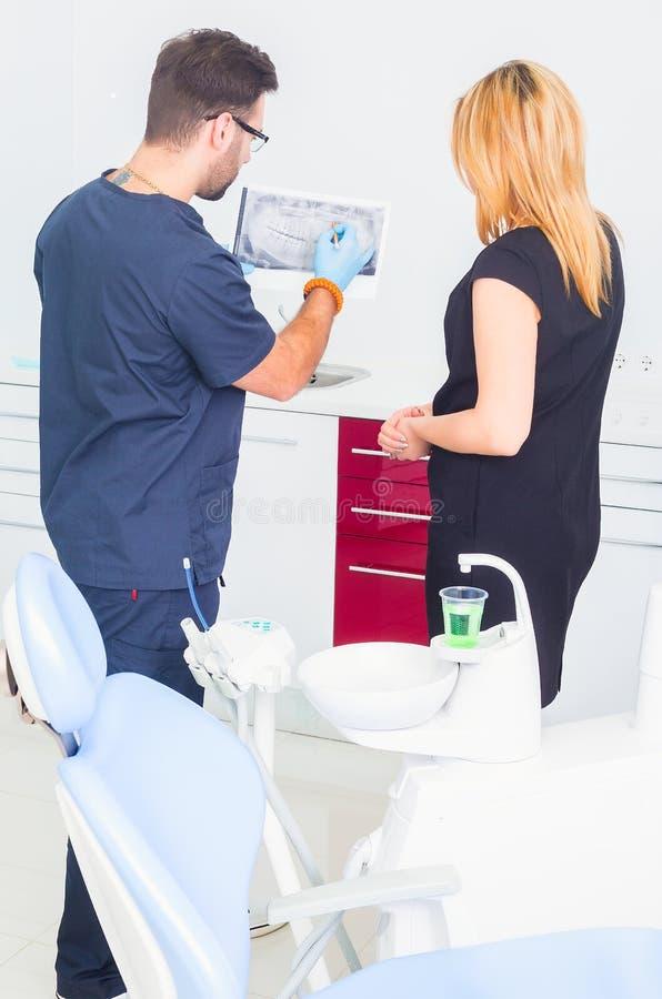 Дантист объясняя изображение луча x к пациенту стоковая фотография