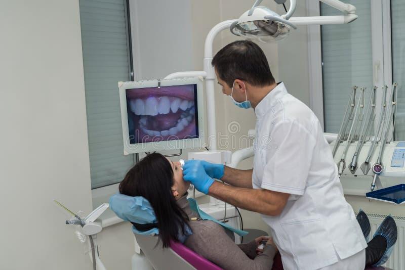 Дантист проверяя зубы пациента с камерой в стоматологии стоковое фото