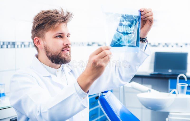 Дантист проверяя результат рентгеновского снимка стоковая фотография rf