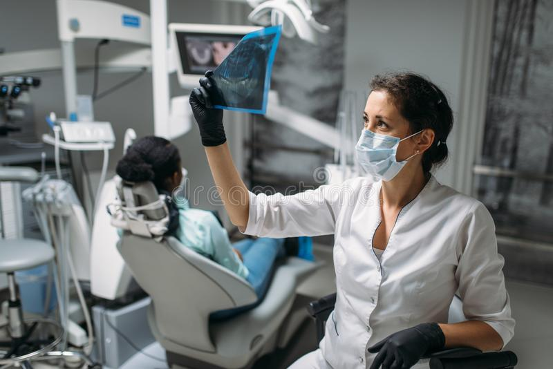 Дантист смотря на изображении рентгеновского снимка, зубоврачебной клинике стоковое фото rf