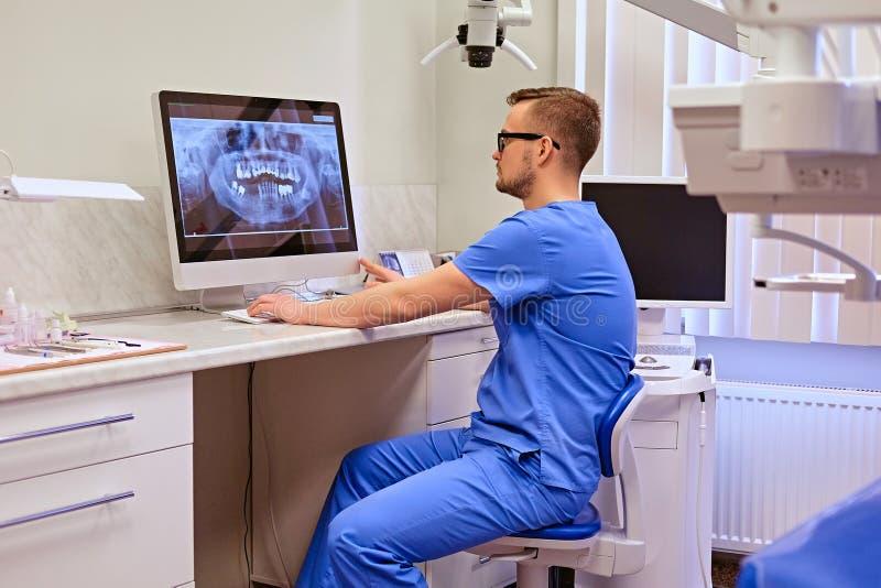 Дантист смотря рентгеновский снимок зубов на компьютере в офисе дантиста стоковое изображение rf