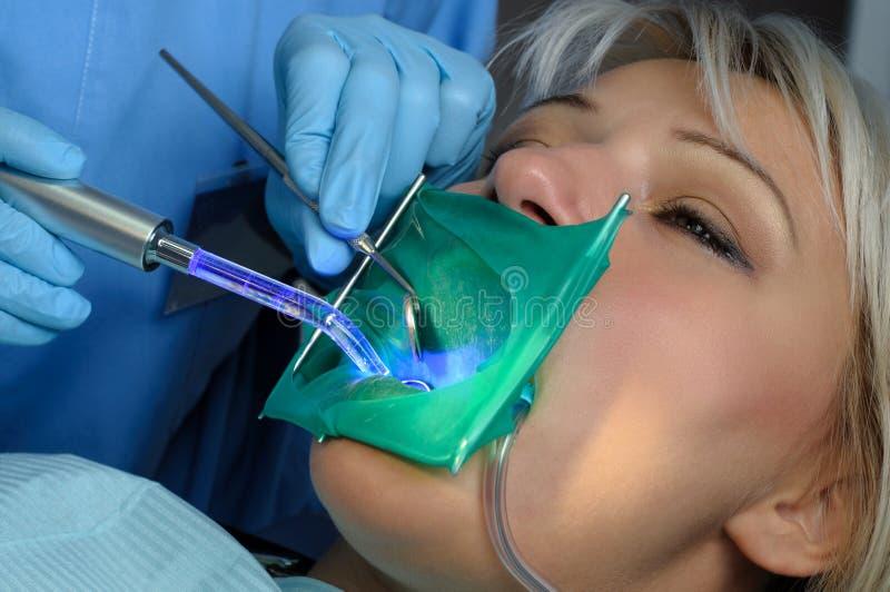 Дантист с пациентом, используя зубоврачебный леча свет стоковые фотографии rf