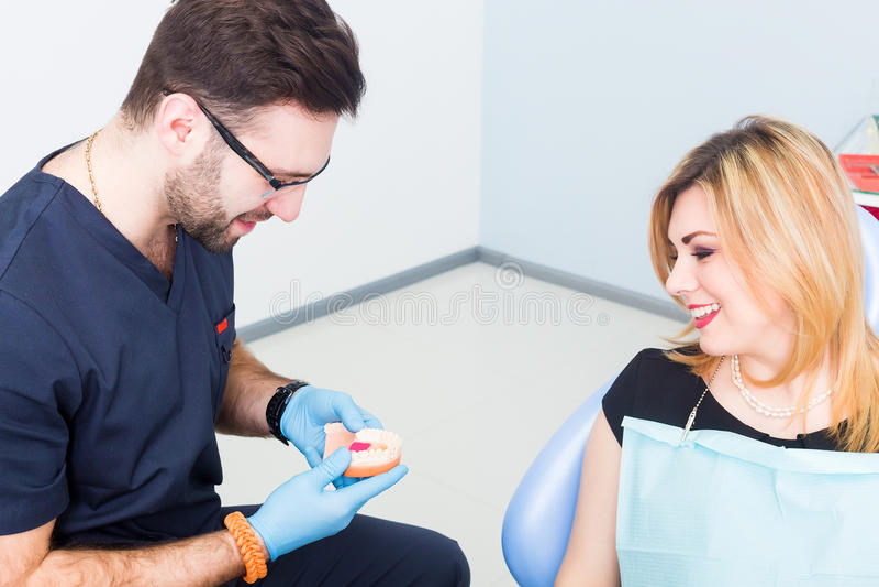 Дантист explaing зубоврачебная обработка с denture к женскому пациенту стоковое изображение