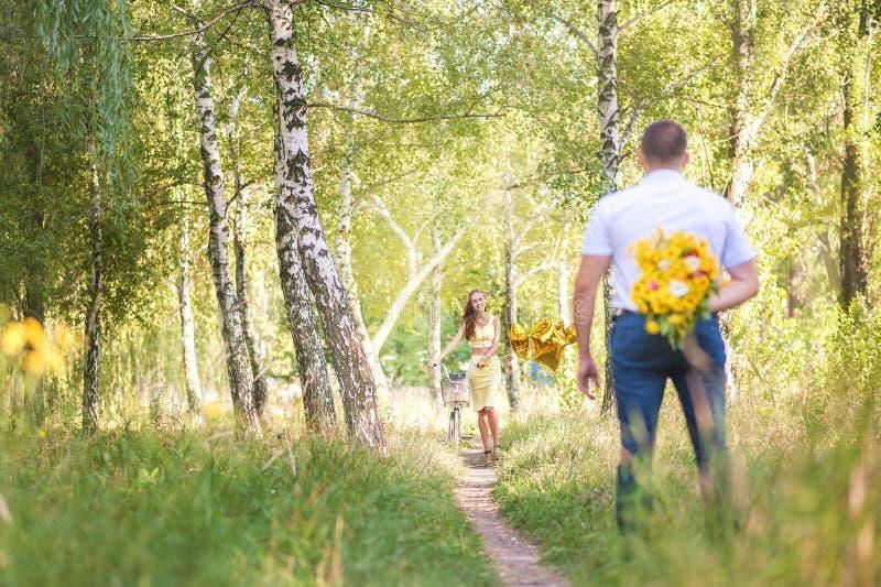 Дата в человеке леса a с цветками его назад ждет женщину на велосипеде стоковое изображение rf