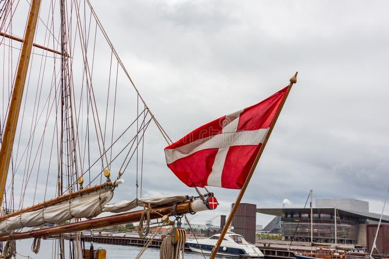 Датский флаг на лете голубого неба стоковая фотография rf