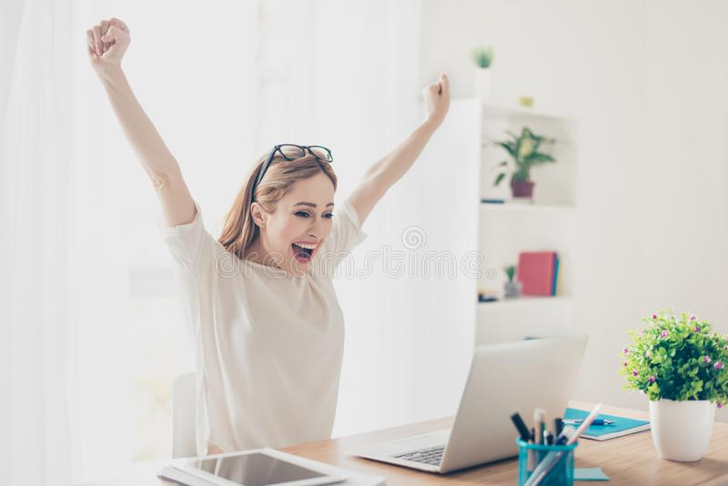 Да! Счастливое excited рабочее место женщины дома торжествуя с rai стоковое фото