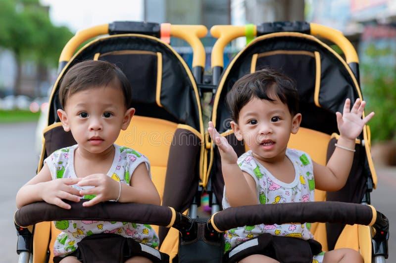 Два брата сидят в коляске Милые мальчики-близнецы сидят в коляске и счастливо улыбаются Детские эмоции стоковое изображение