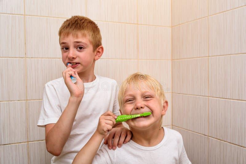 Два мальчика тщательно чистят зубы в ванной Удобная гигиена стоковое изображение rf