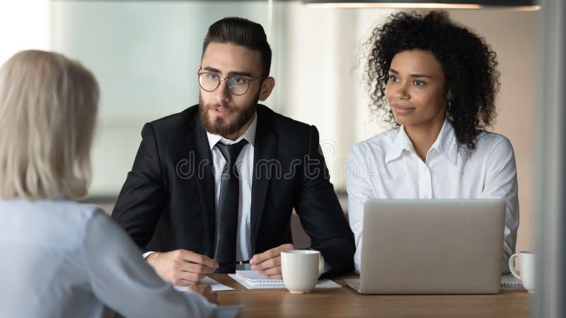 Два разных менеджера проводят собеседование с взрослым кандидатом стоковые фото