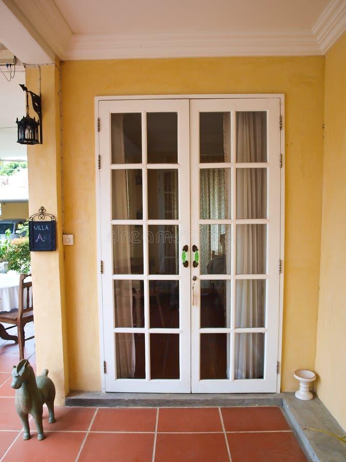 Двери двойного патио белые французские с окнами на желтой стене стоковые фото