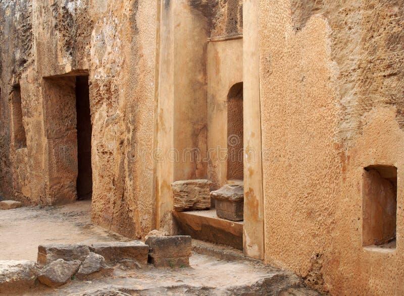 Двери и ниши усыпальницы в высекаенной стене песчаника формируя улицу как взгляд в виске зоны королей в paphos Кипре стоковые фото