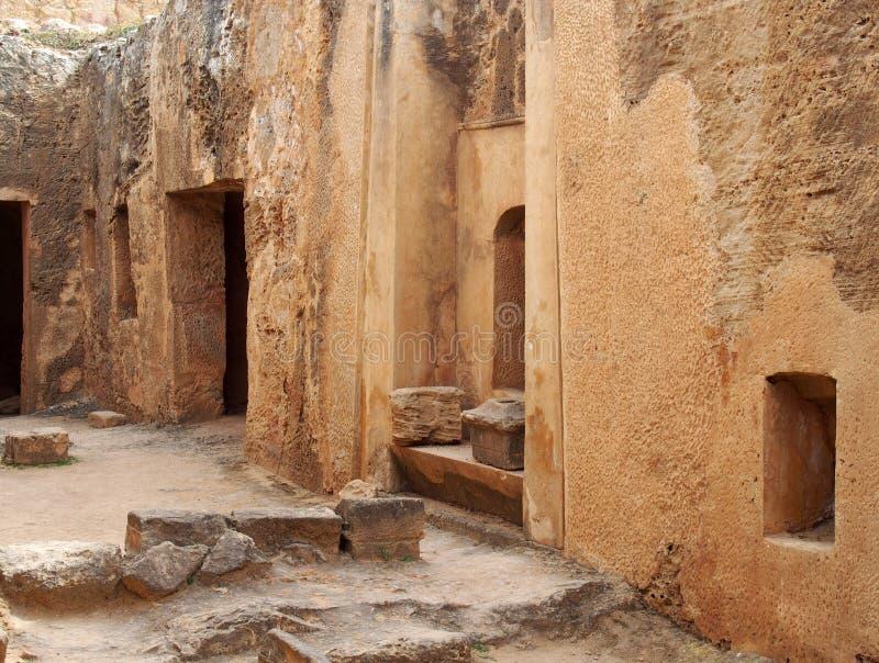 Двери и ниши усыпальницы в высекаенной стене песчаника формируя улицу как взгляд в виске зоны королей в paphos Кипре стоковое фото