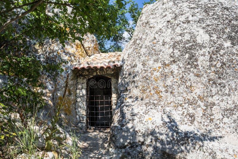Двери к дому в утесе огромный камень на переднем плане стоковая фотография rf