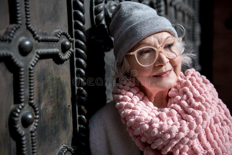 Двери радостной зрелой женщины расслабляющие близко архитектурноакустические стоковое фото