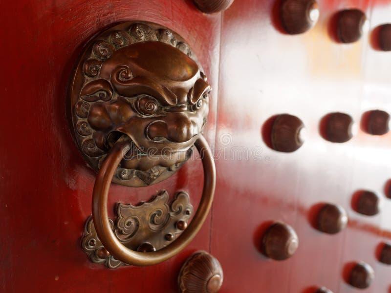 Двери традиционного китайския с латунью регулируют символическое голов льва стоковая фотография