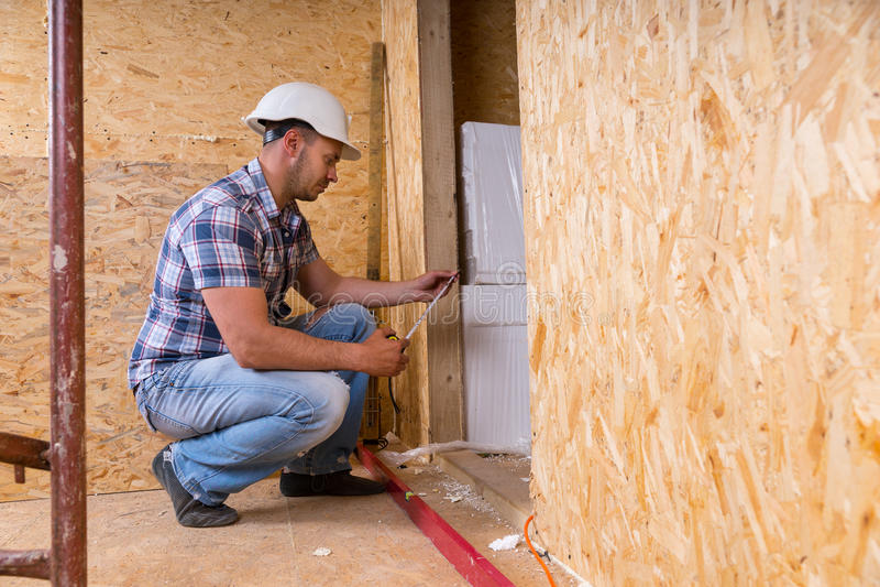 Дверная рама построителя измеряя в незаконченном доме стоковое фото