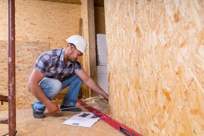 Дверная рама построителя измеряя в незаконченном доме стоковые изображения