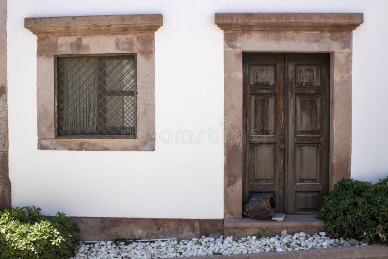 Дверь и окно дома внешняя Белые и коричневые цвета старые баки перед дверью Оно было вытягивано через улицу стоковое изображение rf