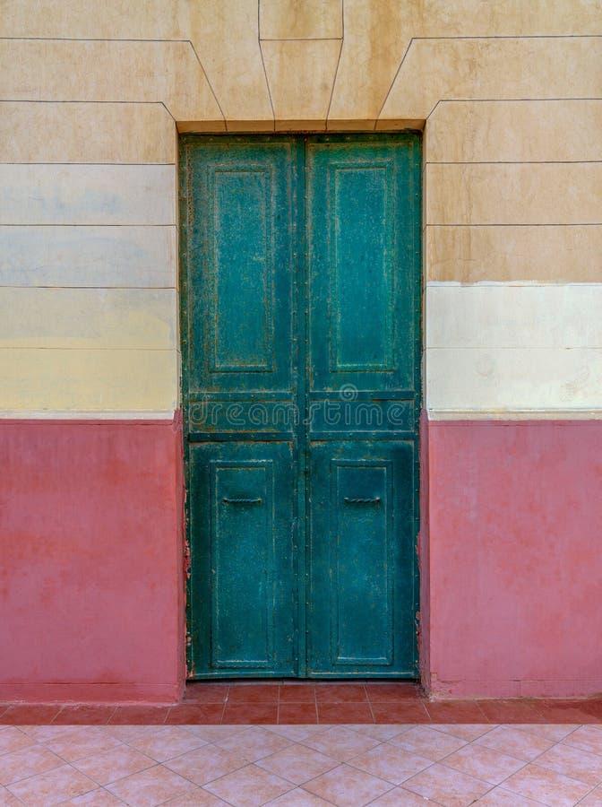 Дверь старого зеленого цвета grunge деревянная в старой стене покрашенной в бежевом и красной стоковое изображение rf