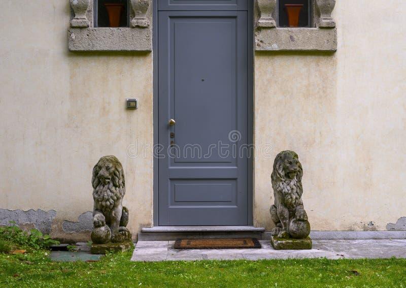 Дверь фланкированная статуями льва попечителя в саде дома Atellani, Museo Vigna di Leonardo, Милан стоковая фотография rf