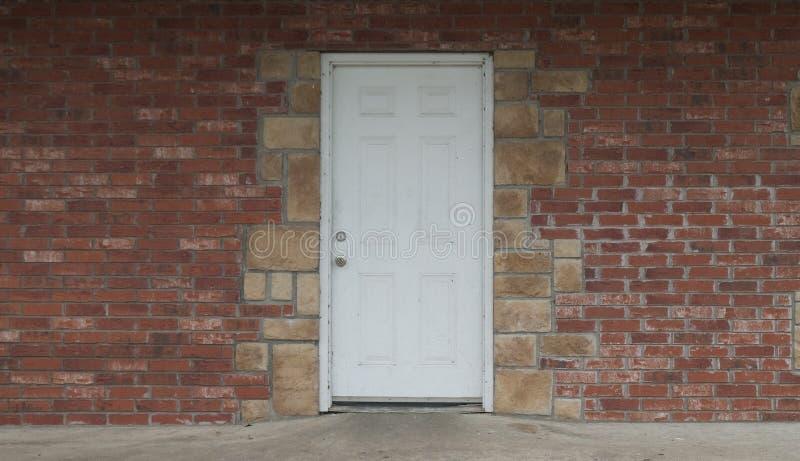 Дверь Grunge белая в кирпиче и каменной стене стоковое изображение