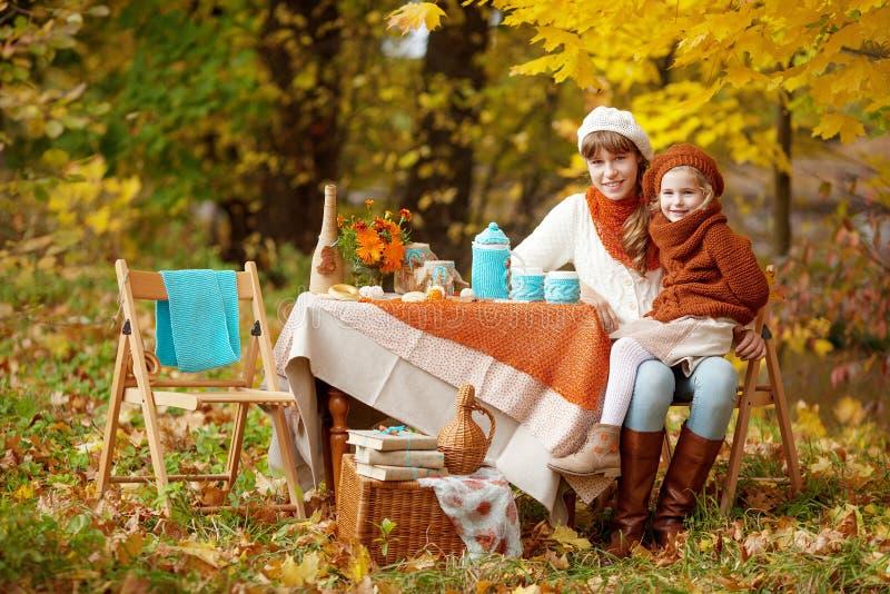 Две милые сестры на пикнике в осеннем парке Очаровательные маленькие девочки, которые выпивают чай на улице в осеннем саду Девочк стоковая фотография