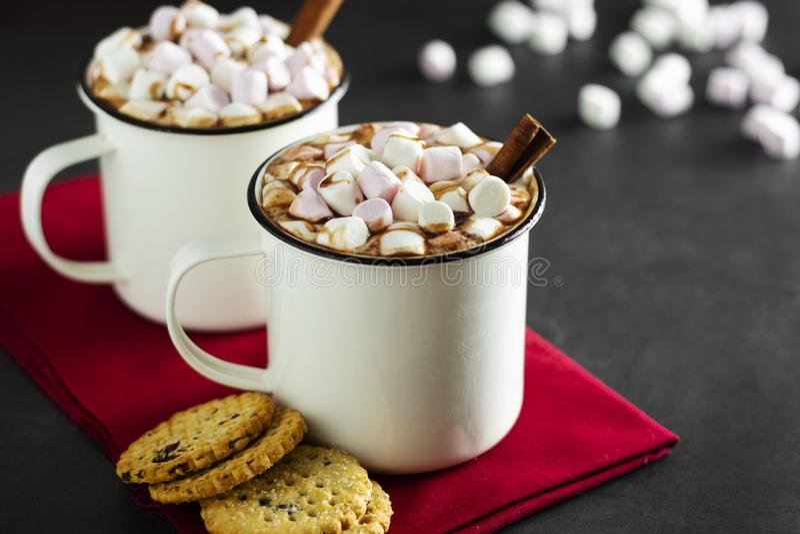 Две чашки горячего шоколада, какао или горячего напитка с зефирами и сладкими печеньками на темном фоне стоковое фото rf