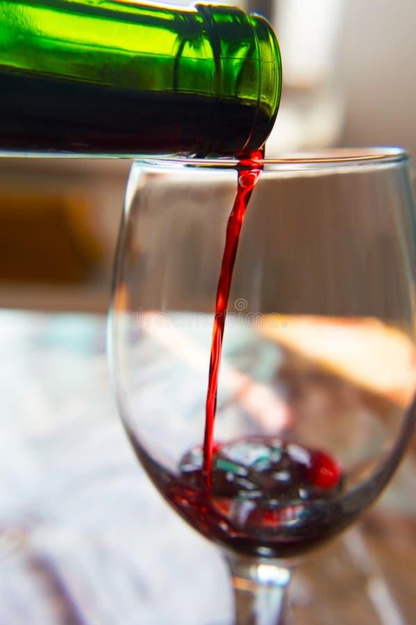 Двигатель красного холодного вина лить от бутылки в стекло стоковые фото