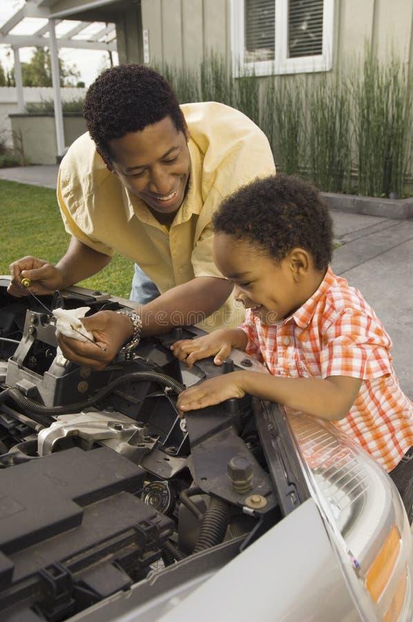 Двигатель автомобиля отца и сына рассматривая в дворе стоковое фото