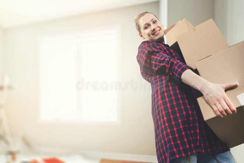 Двигать в новый дом - усмехаясь коробки нося молодой женщины стоковое изображение
