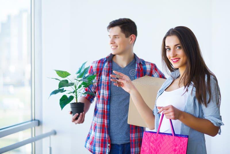 Двигать к новой квартире Счастливые пары и картонная коробка семьи стоковая фотография