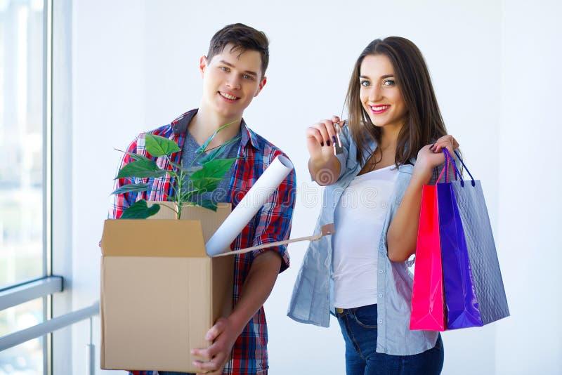 Двигать к новой квартире Счастливые пары и картонная коробка семьи стоковое фото