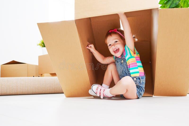 Двигать к новой квартире счастливый ребенок в картонной коробке стоковое фото rf