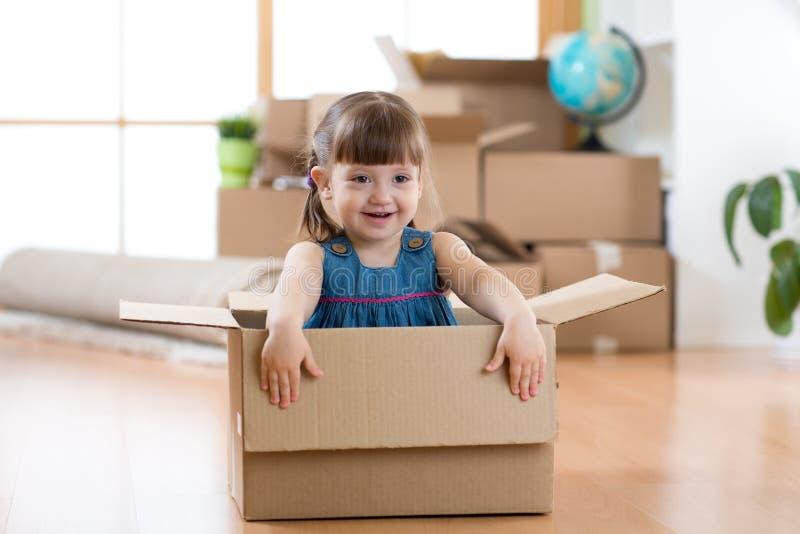 Двигать к новой квартире счастливый ребенок в картонной коробке стоковое изображение