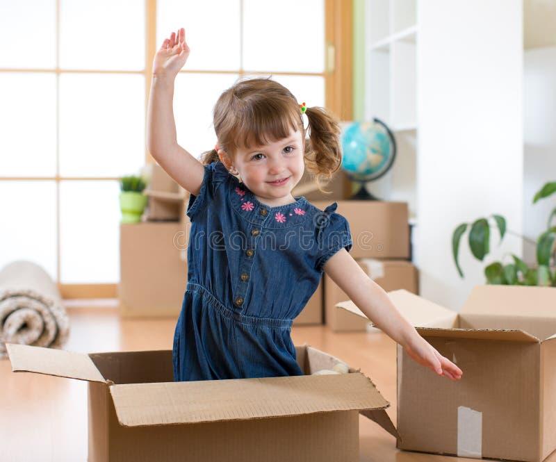 Двигать к новой квартире счастливый ребенок в картонной коробке стоковое изображение rf