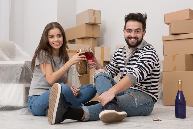 Двигающ внутри, время для утехи, молодой пары празднуя перестановку стоковые фото