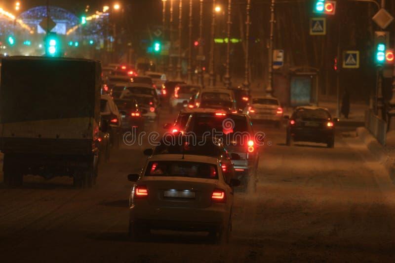 Движение автомобилей в шторме снега зимы на ноче вдоль улицы стоковые фотографии rf