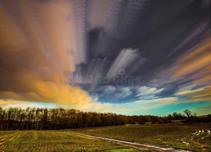 Движение Timelapse облаков к древесинам через поле урожаев стоковое фото rf