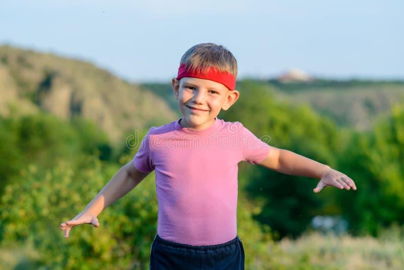 Движения боевых искусств счастливого ребенк практикуя внешние стоковое фото