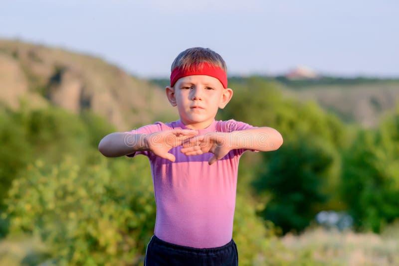 Движения боевых искусств счастливого ребенк практикуя внешние стоковые фотографии rf
