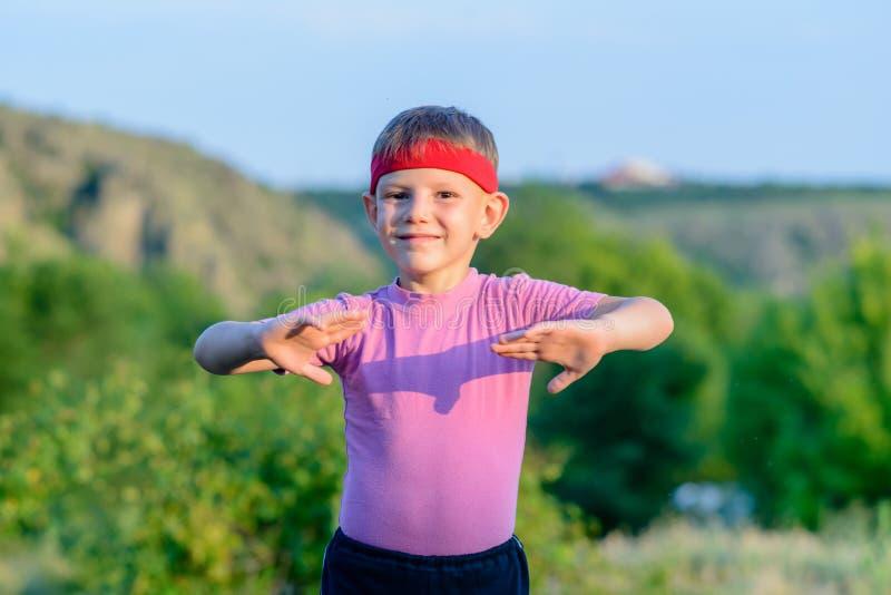 Движения боевых искусств счастливого ребенк практикуя внешние стоковые изображения