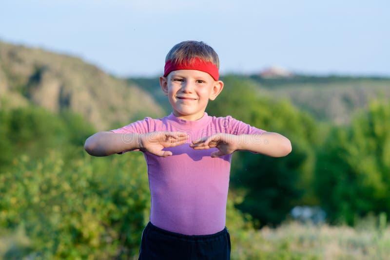 Движения боевых искусств счастливого ребенк практикуя внешние стоковые изображения rf