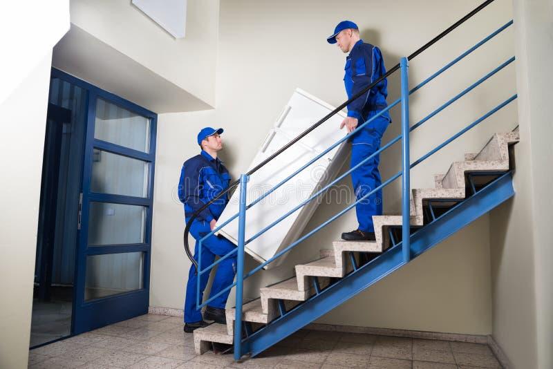 Движенцы нося холодильник на шагах дома стоковые фото