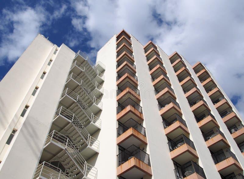 Двинутый под углом взгляд детали жилого дома старых 1960s белого конкретного с шагами и балконов против голубого неба и облаков стоковое фото rf