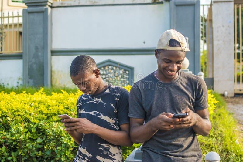 двое молодых чернокожих мужчин пользуются своими мобильными телефонами на открытом воздухе, пишут смс и просматривают интернет, у стоковое изображение