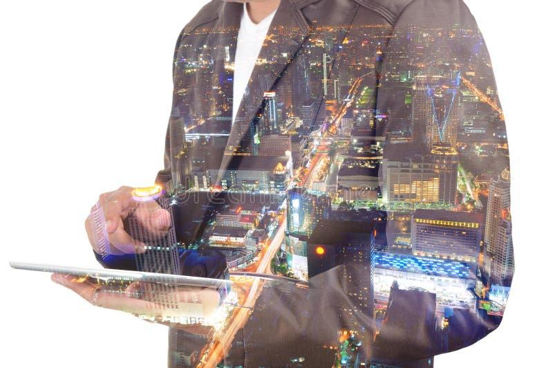 Двойная экспозиция бизнесмена и города используя таблетку сверх стоковое фото rf