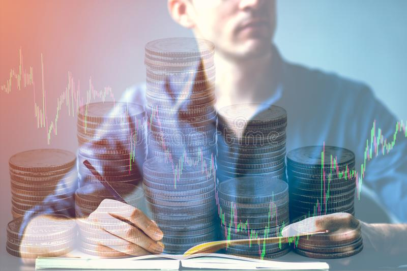 Двойная экспозиция бизнесмена корчась на столе и фондовой бирже или валюты изображают диаграммой и штабелируют монетку соответств стоковая фотография