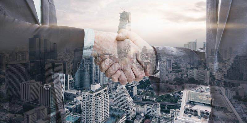 Двойная экспозиция бизнесмена 2 тряся руки с городом в ба стоковые фото